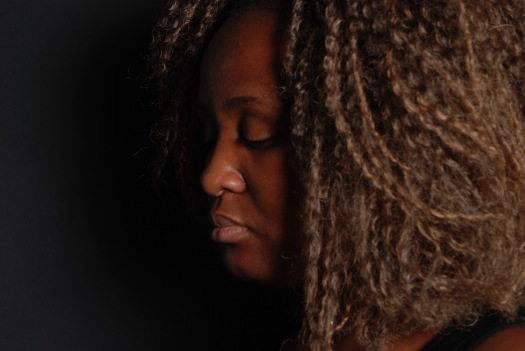 A beautiful black woman side shot photography of just her face and hair with a black backdrop