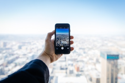Hand holding an iPhone technology with a blurred city skyline in the background